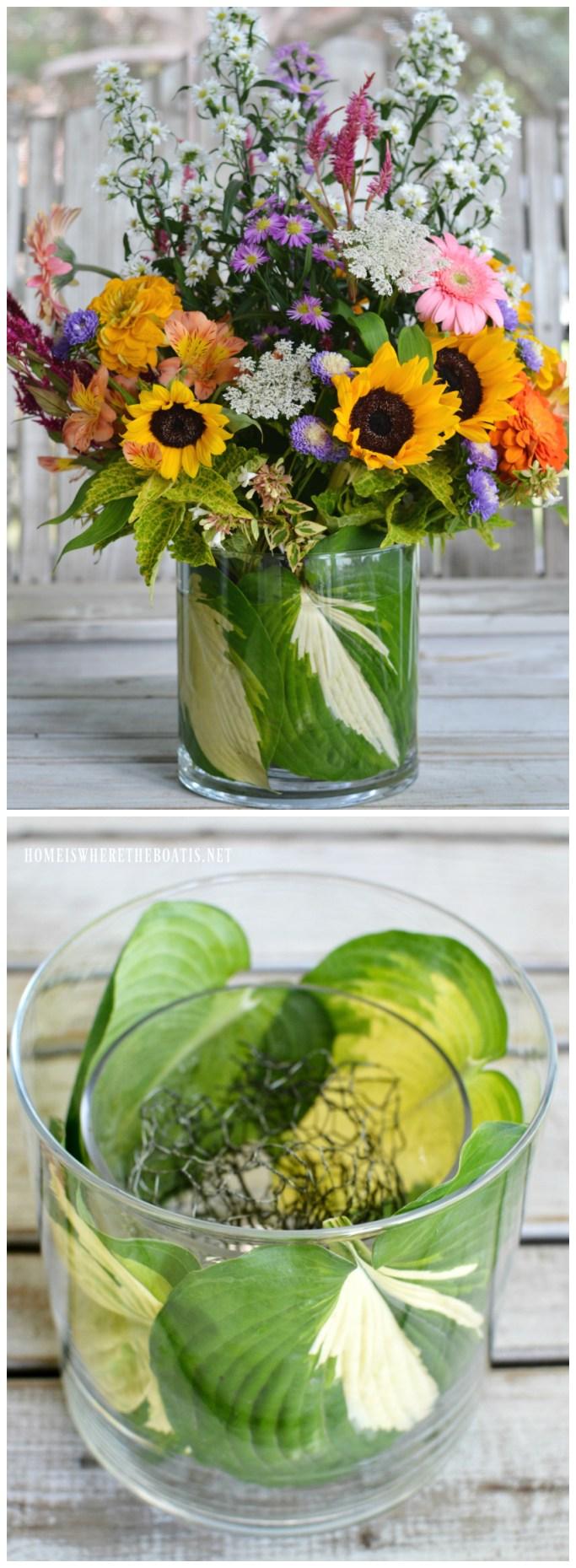 Flower arrangement using hosta leaves to conceal chicken wire in smaller glass vase | ©homeiswheretheboatis.net #flowerarranging #flowers