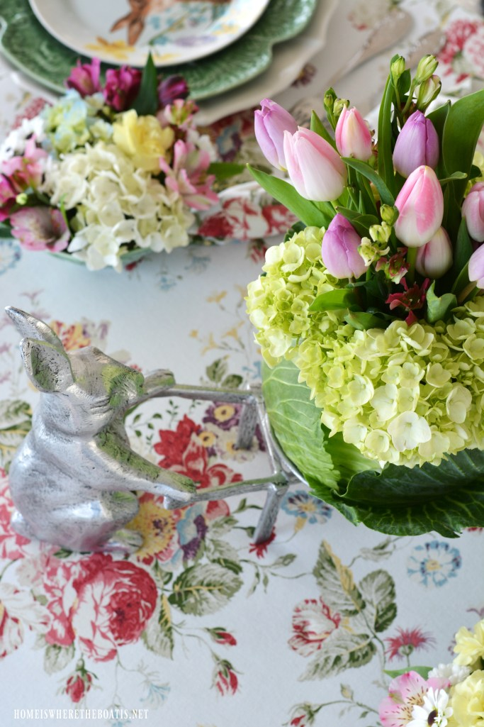 Bunny wheelbarrow with blooming cabbage flower arrangement and table centerpiece | ©homeiswheretheboatis.net #spring #tablescape #bunnies