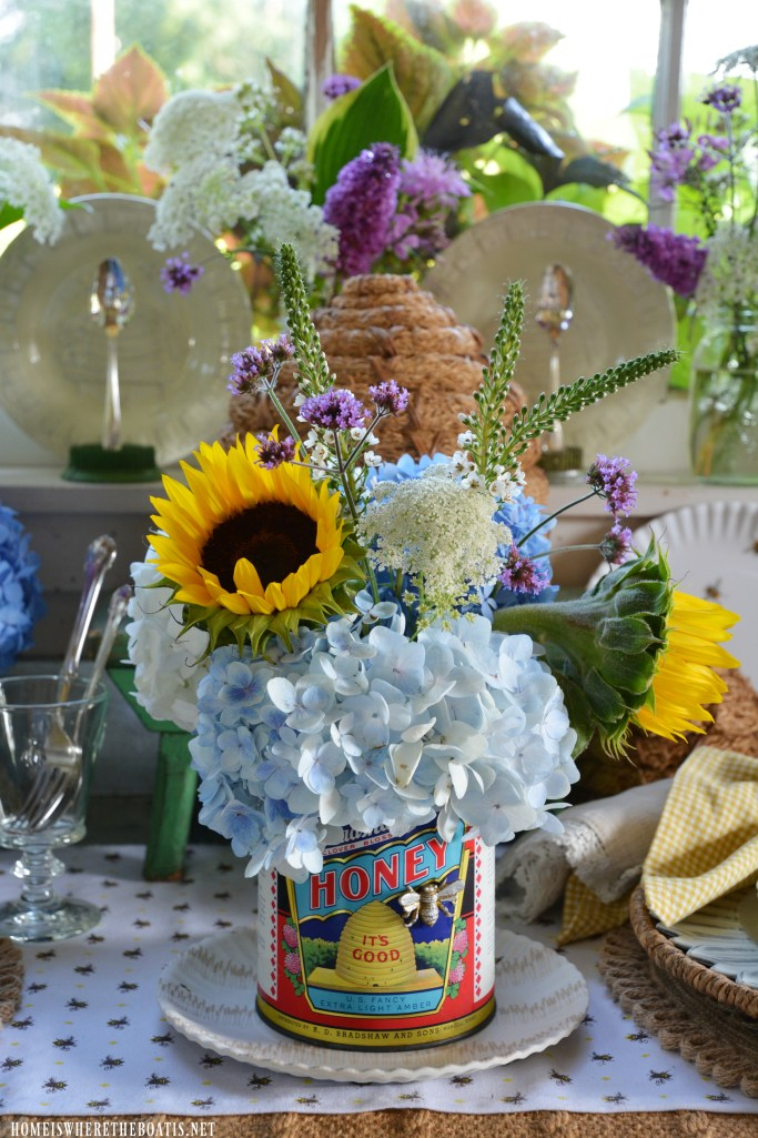 Vintage honey can with flowers and bee table for National Pollinator Week | ©homeiswheretheboatis.net #bees #tablescapes
