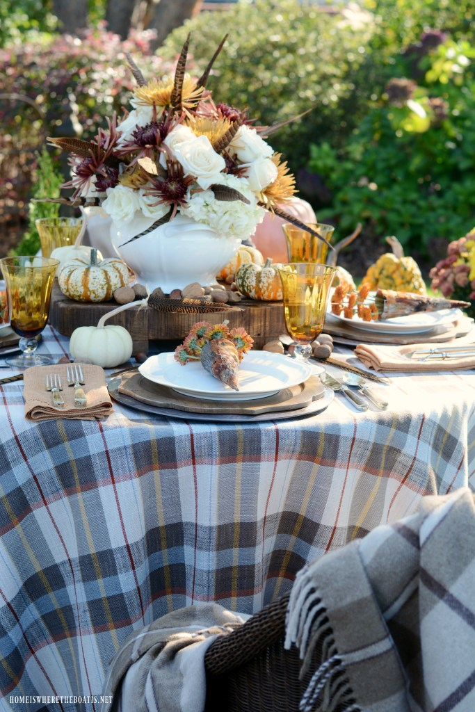 Fall tablescape and flower arrangement with roses, hydrangeas, mums and feathers | ©homeiswheretheboatis.net #fall #tablescape #alfresco #flowers #feathers