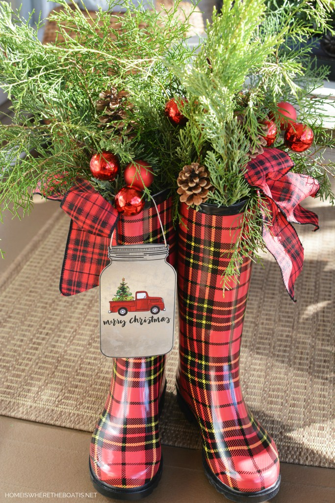 Tartan plaid wellies are filled with a mix of fresh greenery, pine cones, red ornament picks and ribbon | ©homeiswheretheboatis.net #christmas #wellies #porch