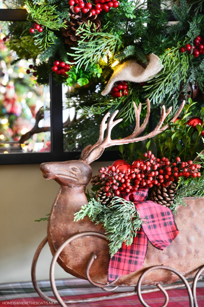Christmas Deer sleigh centerpiece filled with greenery, berries, pine cones and ribbon | ©homeiswheretheboatis.net #christmas #greenery #deer