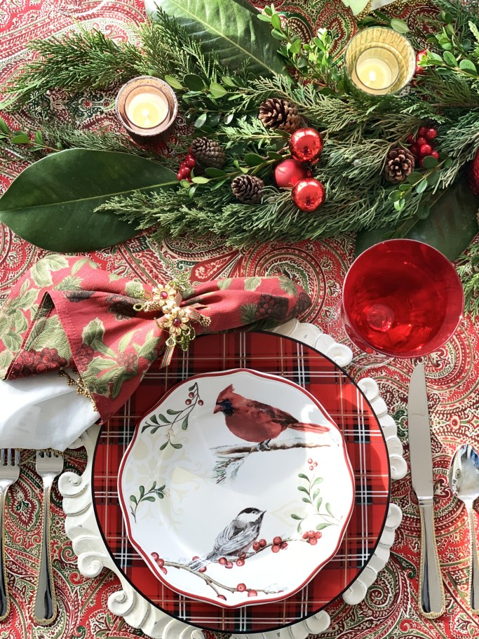 Christmas table with bird plates and evergreen runner | ©homeiswheretheboatis.net #Christmas #tablescapes