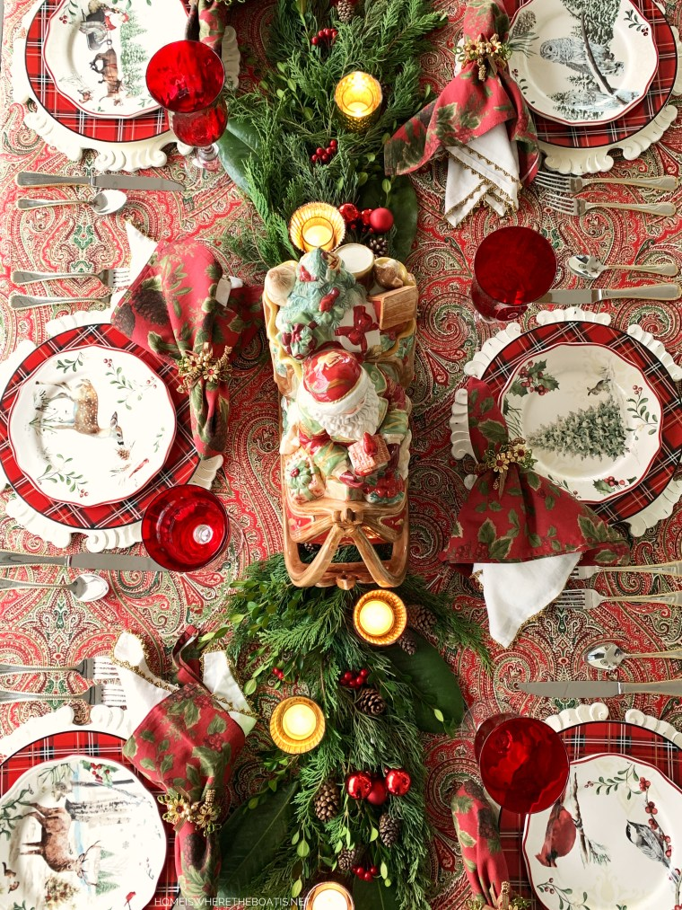 Christmas Table with red and green paisley tablecloth and evergreen runner | ©homeiswheretheboatis.net #Christmas #tablescapes