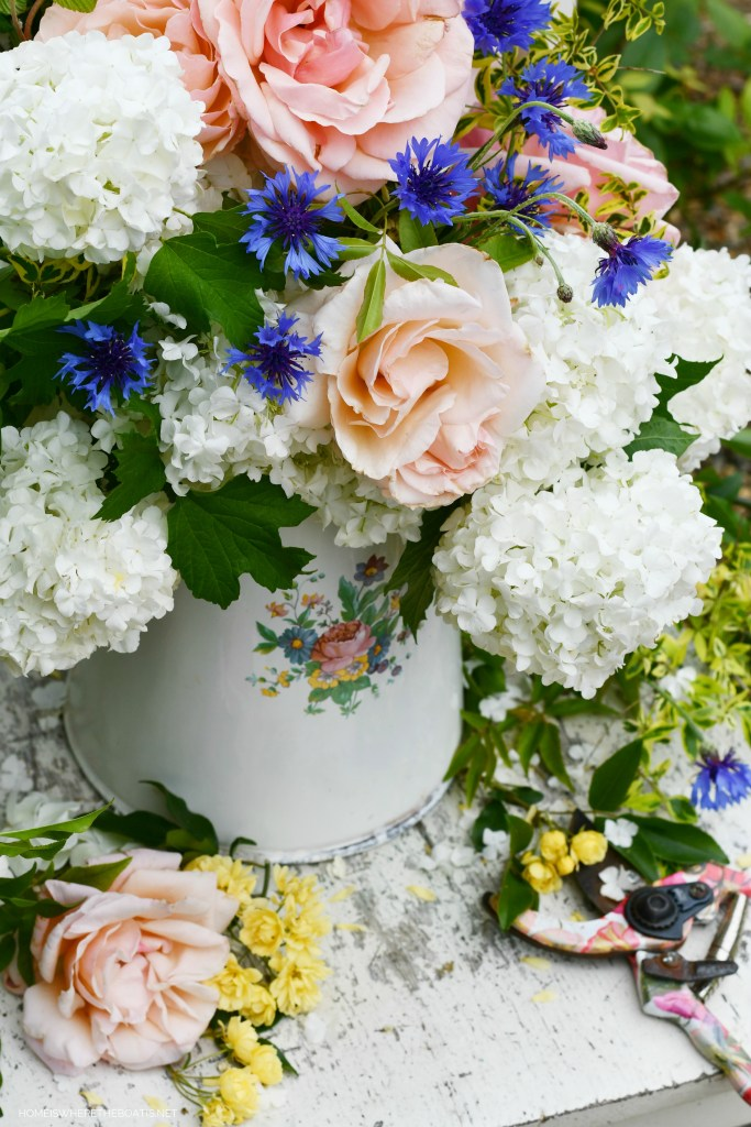 Vintage enamelware pitcher with garden flowers | ©homeiswheretheboatis.net #garden #flowers #spring #arrangement #roses