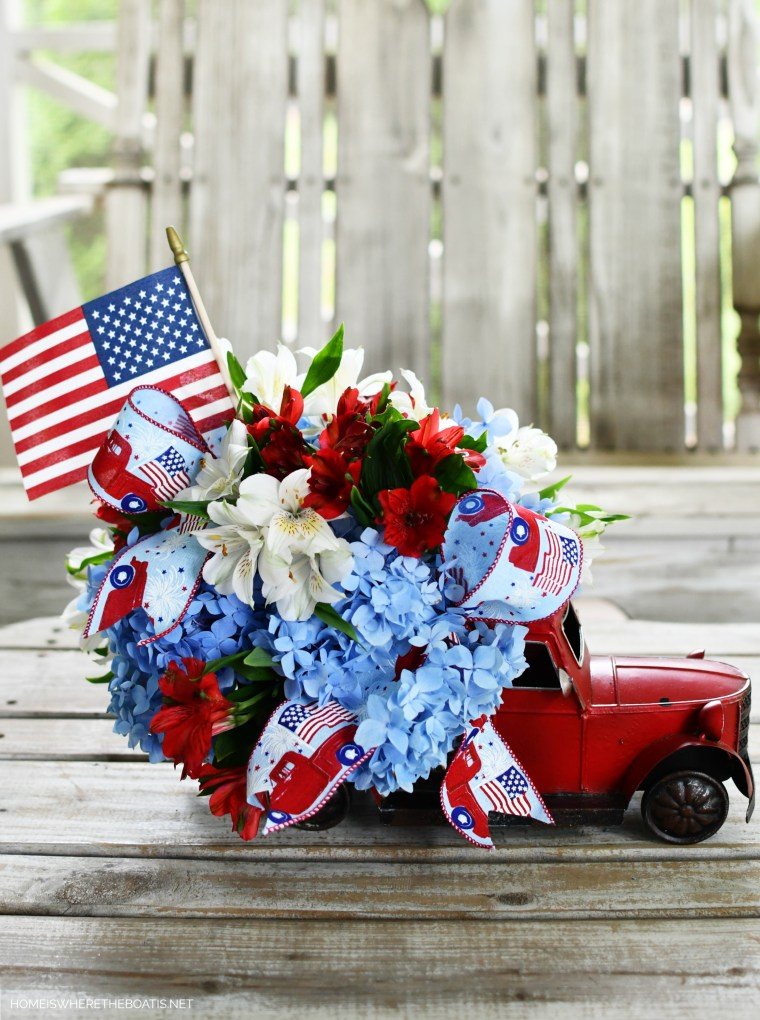 DIY patriotic flower centerpiece with a red truck and flag | ©homeiswheretheboatis.net #patriotic #tablescape #centerpiece #flag #4thofjuly