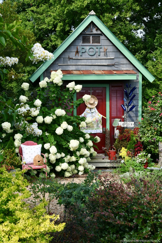 A back door welcome buzzing with bees, a bonnet and apron door decor for Potting Shed | ©homeiswheretheboatis.net #flowers #garden