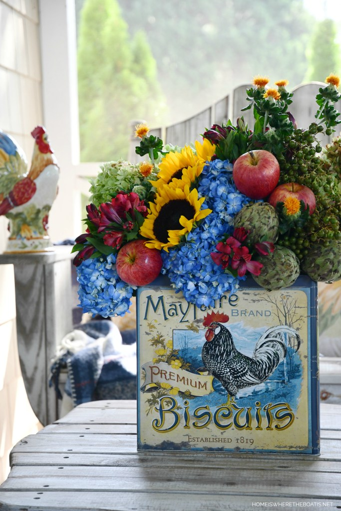 Biscuit tin with rooster transitional flower arrangement with hydrangeas, sunflowers, apples and artichokes | ©homeiswheretheboatis.net #hydrangeas #sunflowers #rooster