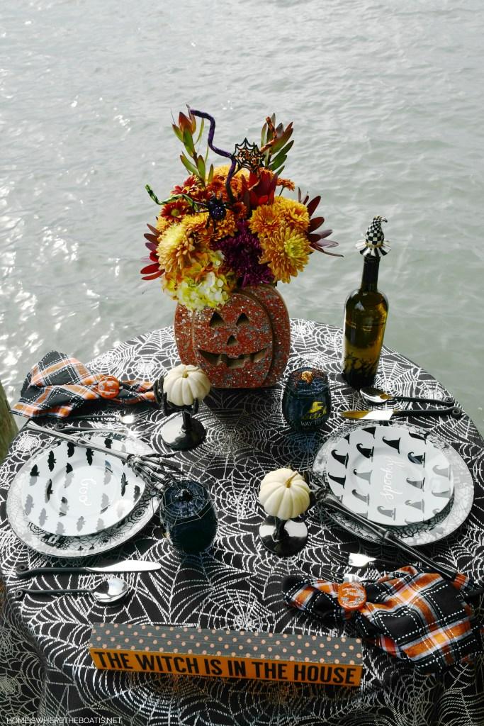 Halloween table on dock of lake | ©homeiswheretheboatis.net #halloween #tablescape #skeleton