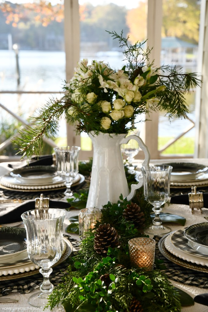 Christmas tablescape with pitcher centerpiece, evergreen runner and black and white checks | ©homeiswheretheboatis.net #christmas #tablescapes