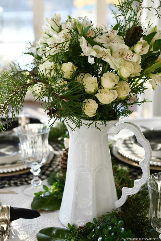 Holiday table with pitcher centerpiece and black and white checks | ©homeiswheretheboatis.net #christmas #tablescapes