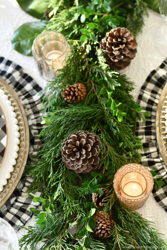 Holiday table with evergreen and pinecone runner | ©homeiswheretheboatis.net #christmas #tablescapes
