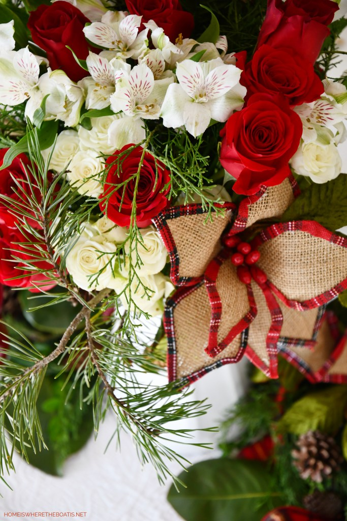 Flower arrangement centerpiece with burlap and tartan trimmed poinsettia | ©homeiswheretheboatis.net #christmas #tablescapes #tartan #plaid