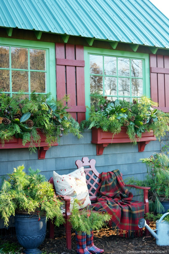 Sprucing up the Potting Shed window boxes for Christmas with greenery, pine cones and rusty metal jingle bell garland | ©homeiswheretheboatis.net #PottingShed #Christmas #greenery #windowboxes