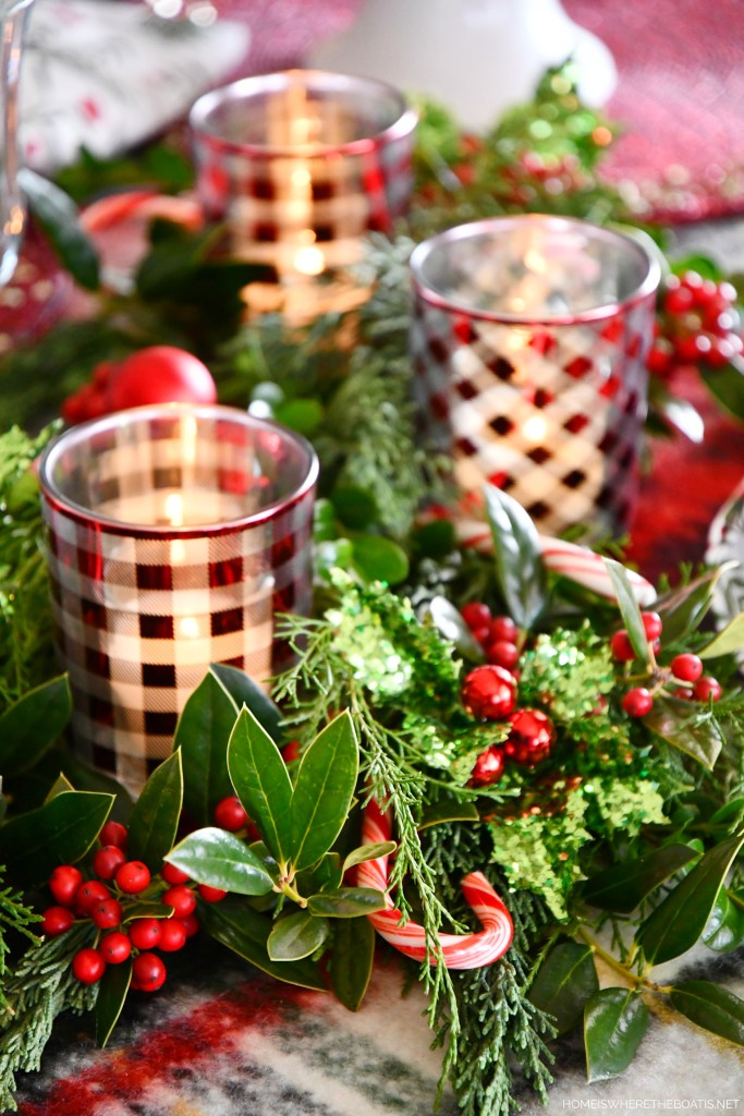 Christmas table with checked votives, greenery and candy canes | ©homeiswheretheboatis.net #christmas #snowman #tablescape