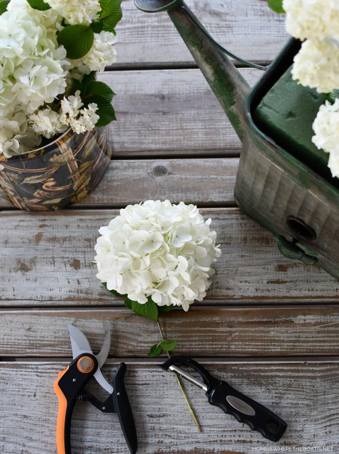 Watering Can Planter flower arrangement | ©homeiswheretheboatis.net #spring #flowers #garden