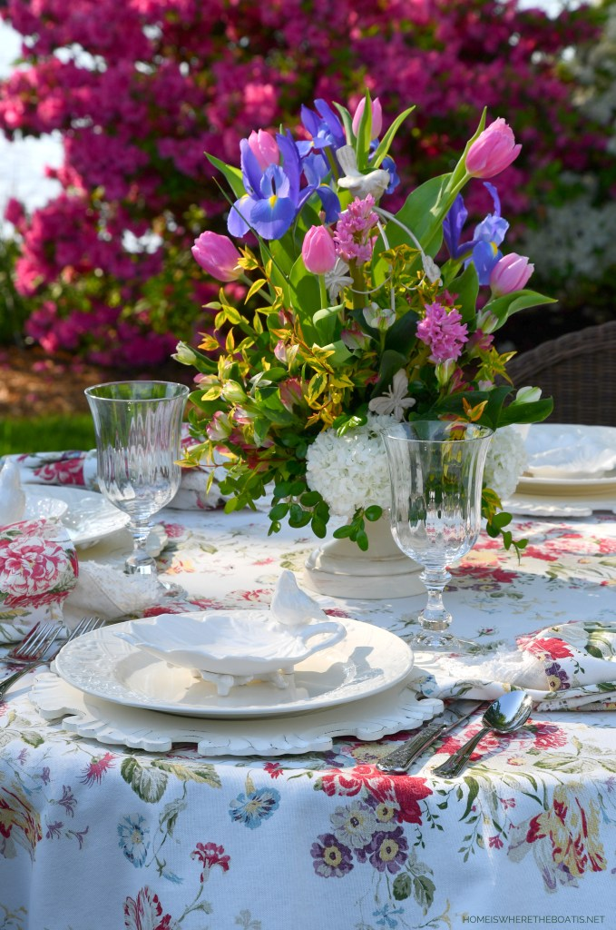 Spring alfresco table with decorative bird cage flower arrangement | ©homeiswheretheboatis.net #spring #flowers #diy #tablescape #alfresco