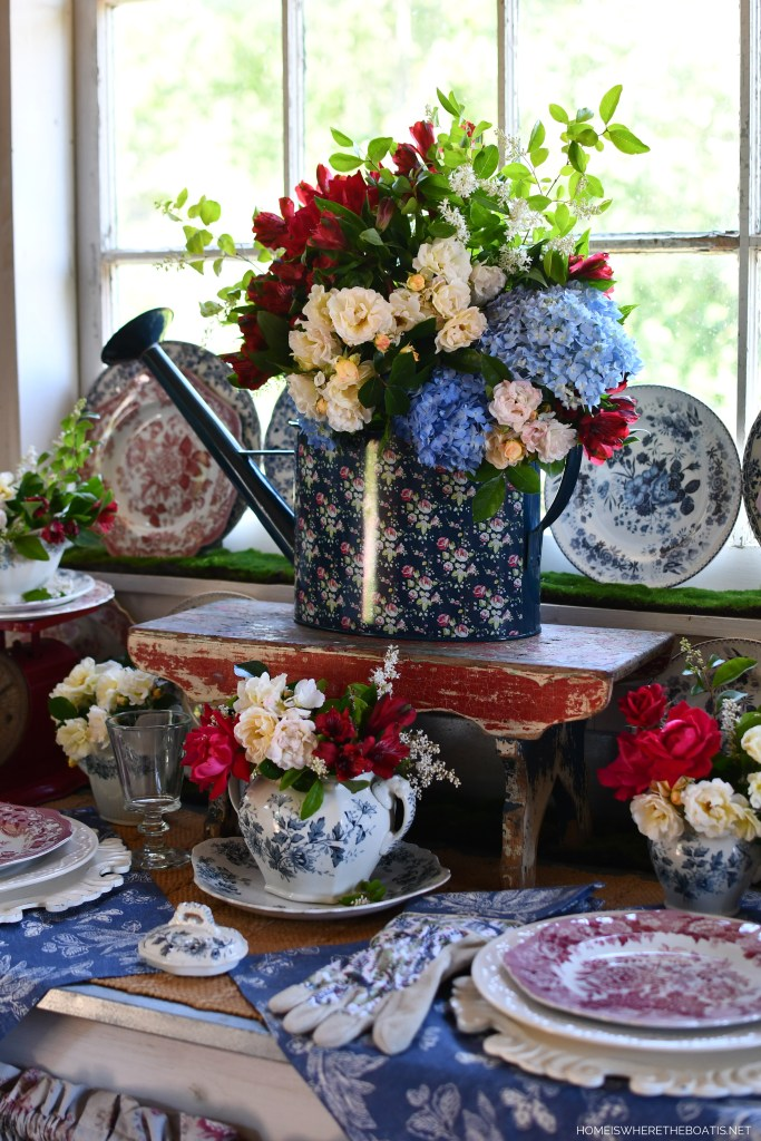 Floral watering can as a vase for flowers | ©homeiswheretheboatis.net #redwhiteandblue #transferware #flowers #tablescape #memorialday