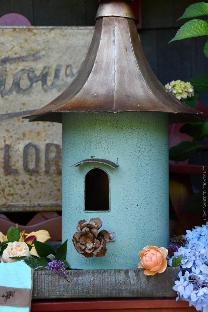 Decorative Birdhouse and Summer Garden Blooms Around the Potting Shed | ©homeiswheretheboatis.net #summer #garden #flowers #daylilies #hydrangeas #bees #butterflies