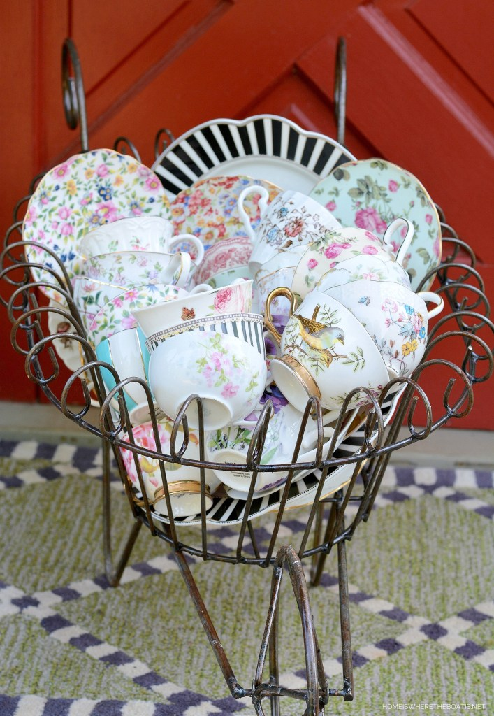 Wheelbarrow of teacups for Alice in Wonderland inspired table and Mad Tea Party | ©homeiswheretheboatis.net #teaparty #aliceinwonderland #tablescape