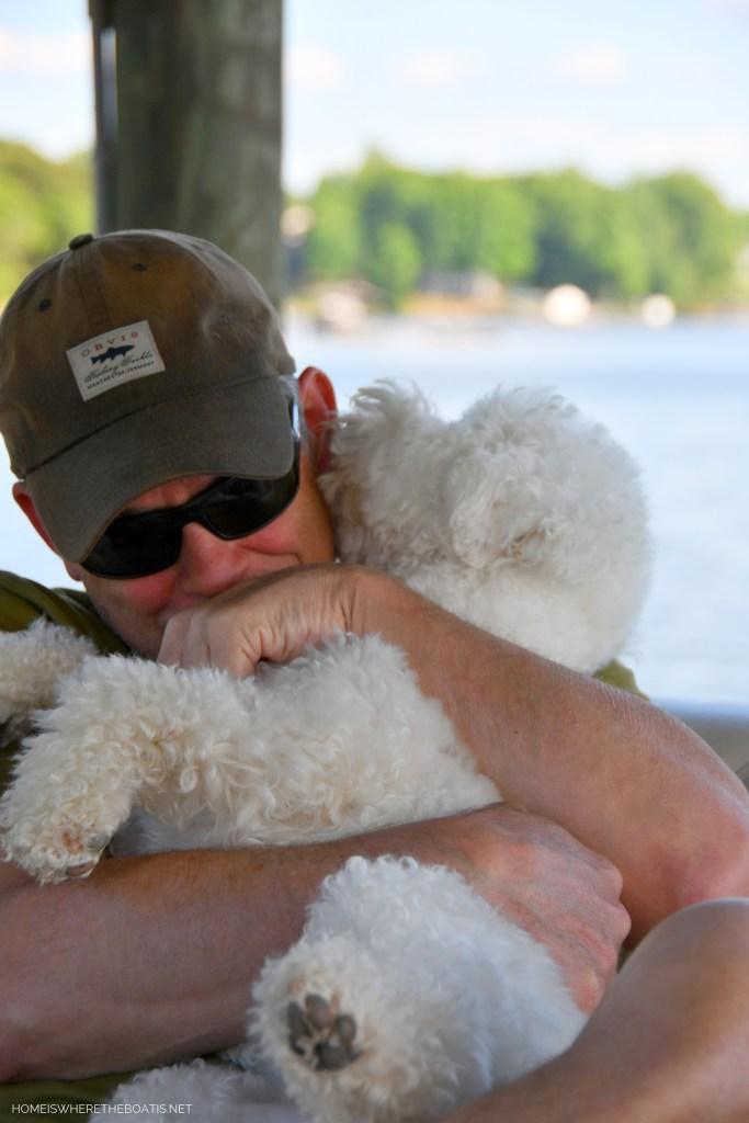 Sophie giving kisses on pontoon | ©homeiswheretheboatis.net #dogs #bichonfrise #nationaldogday