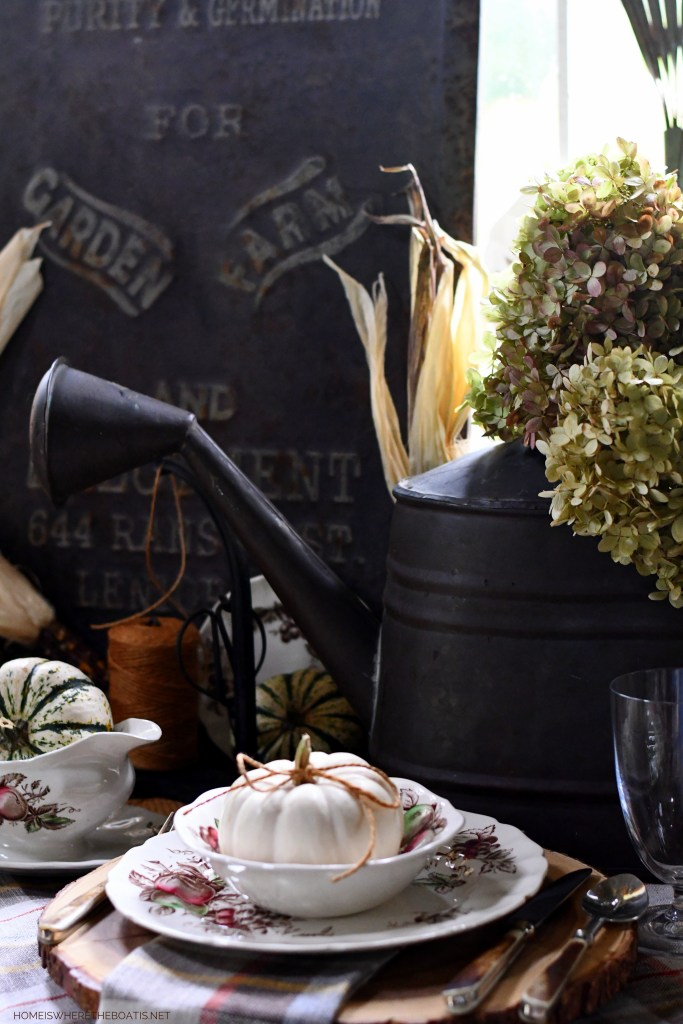 Vintage garden tools with watering can of hydrangeas in the Potting Shed tablescape | ©homeiswheretheboatis.net #garden #fall #harvest #tablescape #pottingshed