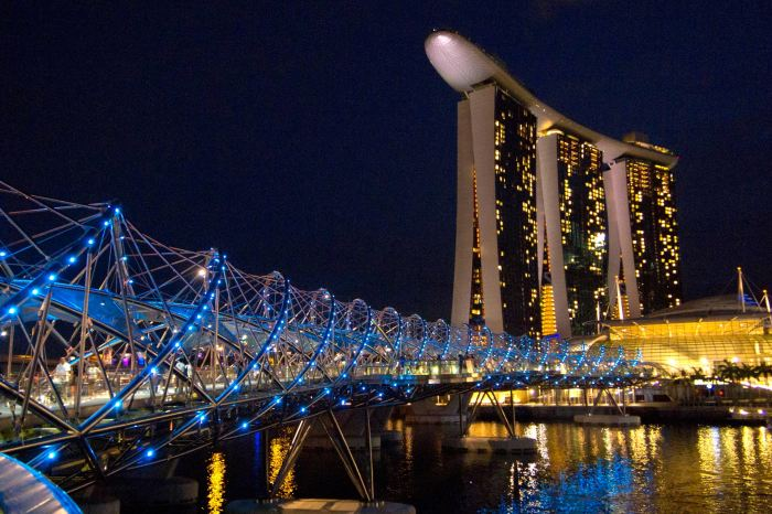 Die Helix Bridge am Marina Bay bei Nacht, im Hintergrund das Marina Bay Sands