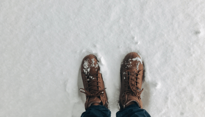A pair of boots in the snow near a home in January.