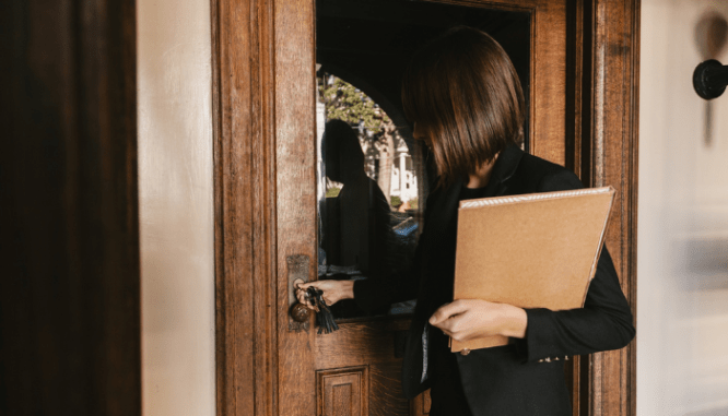 A real estate agent opening the door for a client.