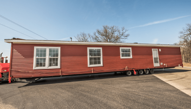 A manufactured home being towed to a new location.