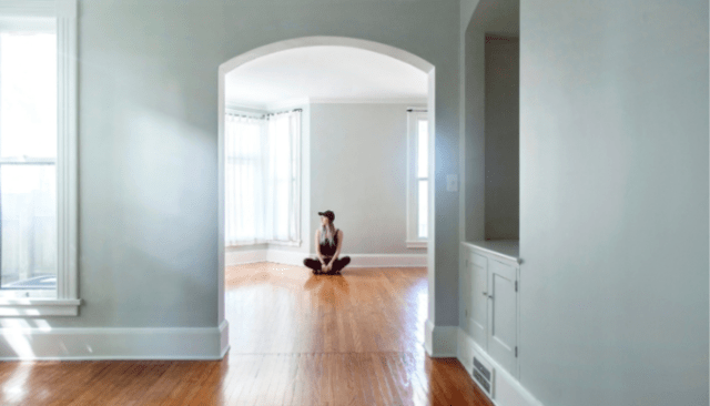 An image of a woman in an empty house meant to depict selling a rental property.