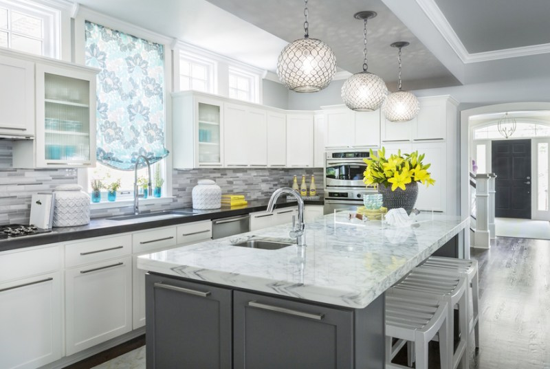 White kitchen with gray marble mosaic tile backsplash. Kitchen with globe pendant lights over grey kitchen island with marble countertop