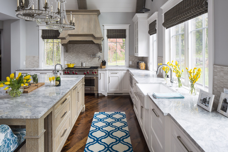 White kitchen with maple floors. Kitchen with candle chandelier over wood kitchen island with marble countertop