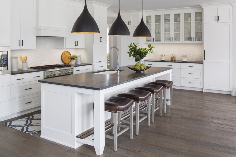 White kitchen with dark hickory wood floors. Kitchen with black pendant lights over white kitchen island with black marble countertop