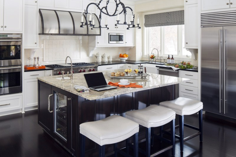 White kitchen with light dark hardwood floors. Kitchen with bar stools with candle pendant light over dark brown kitchen island with marble countertop