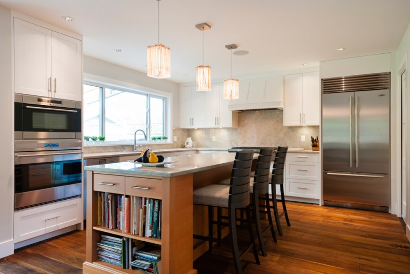 White kitchen with stainless appliances. Kitchen with bar stools with white square pendant lamp over wooden kitchen island with gray marble countertop