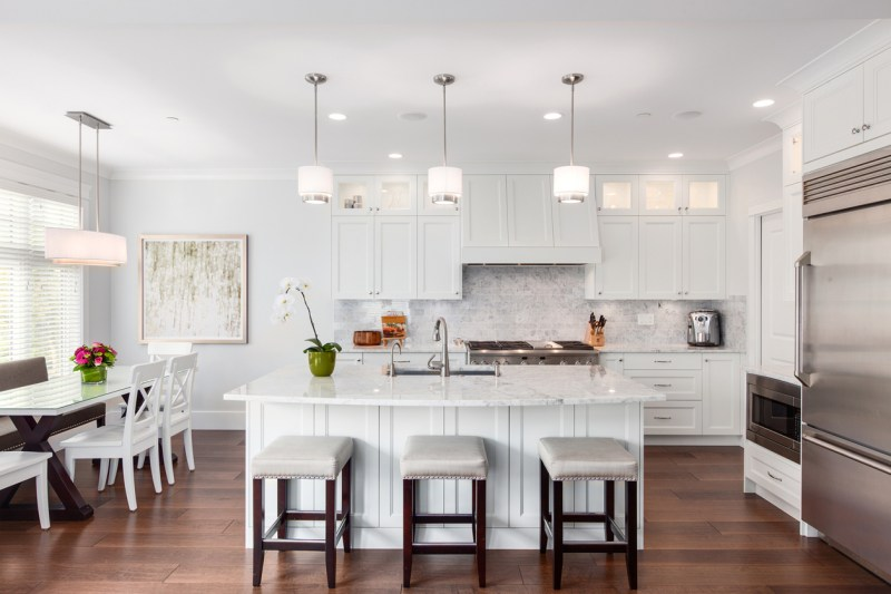 White kitchen design with bar stools, dining area and dark hardwood flooring. Kitchen with small drum pendant light over white kitchen island with white marble countertop