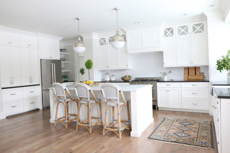 White kitchen with rattan bar stools and hardwood floors. Kitchen with white globe pendant lights over kitchen island with white laminate countertop