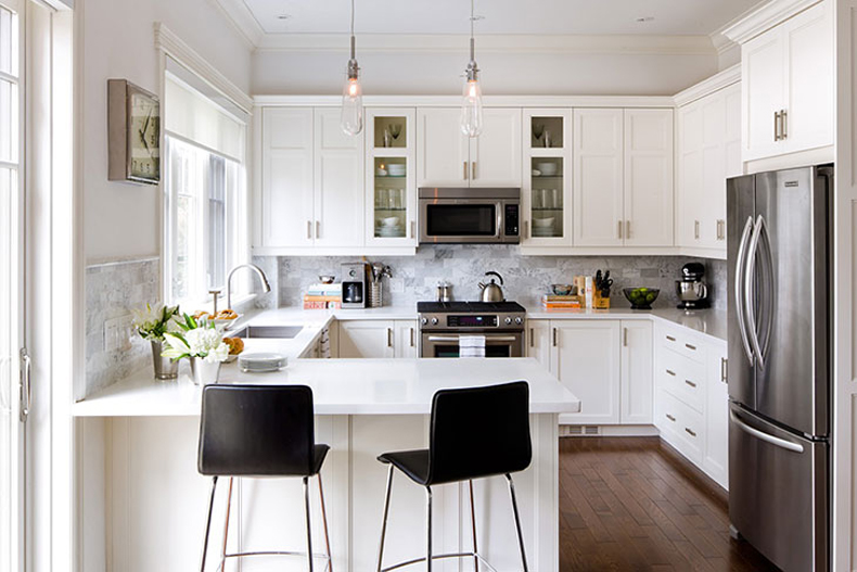 Small white kitchen with gray backsplash and black bar stools. Kitchen with glass tube pendant lights