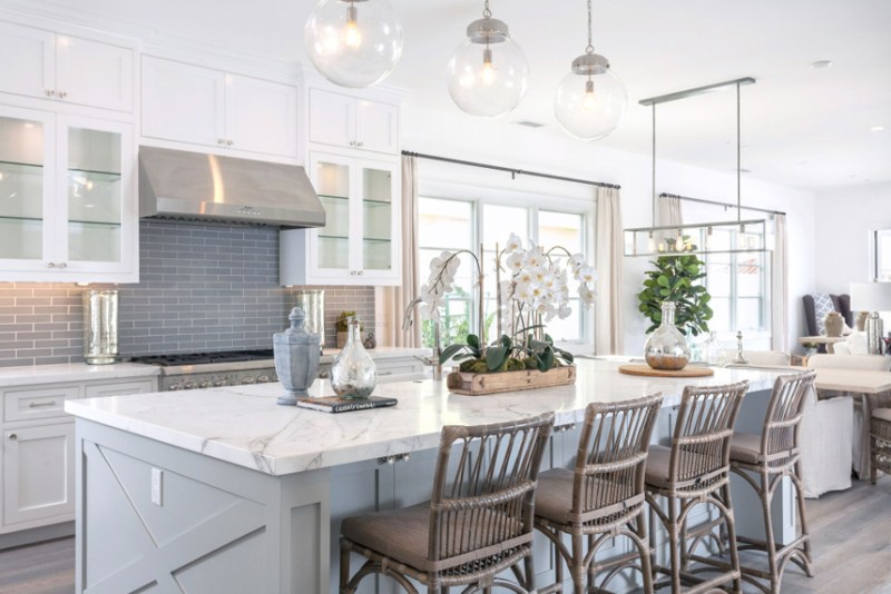 White kitchen with rattan swivel bar stools. Kitchen with glass ball pendant lights over gray kitchen island with marble countertop