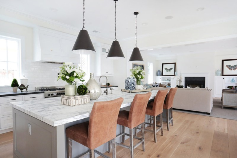 White kitchen with burnt orange bar stools. Kitchen with black pendant lights over gray kitchen island with marble countertops