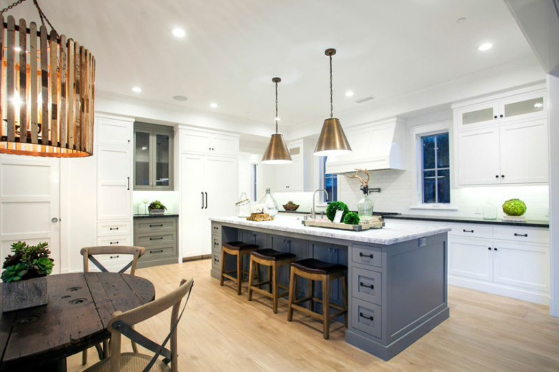 White kitchen with rustic wooden bar stool. Kitchen with gold pendant lights over navy kitchen island with marble countertops