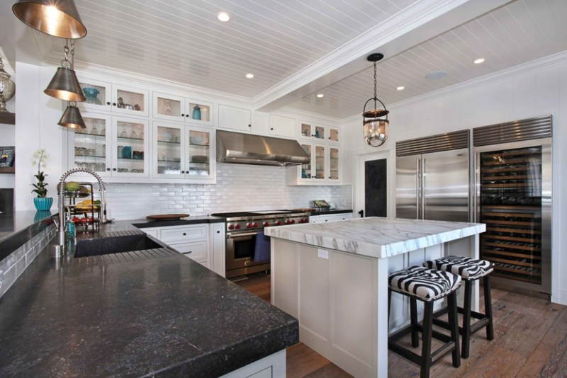 White kitchen with black quartz countertops. Kitchen with glass pendant lights over kitchen island with marble countertops