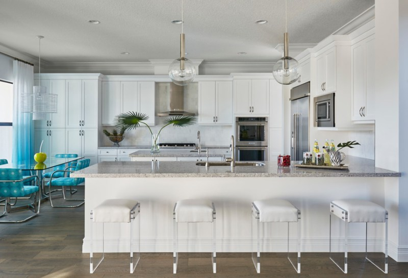 White kitchen with modern white backless bar stools. Kitchen with clear globe pendant lights over kitchen island with marble countertop