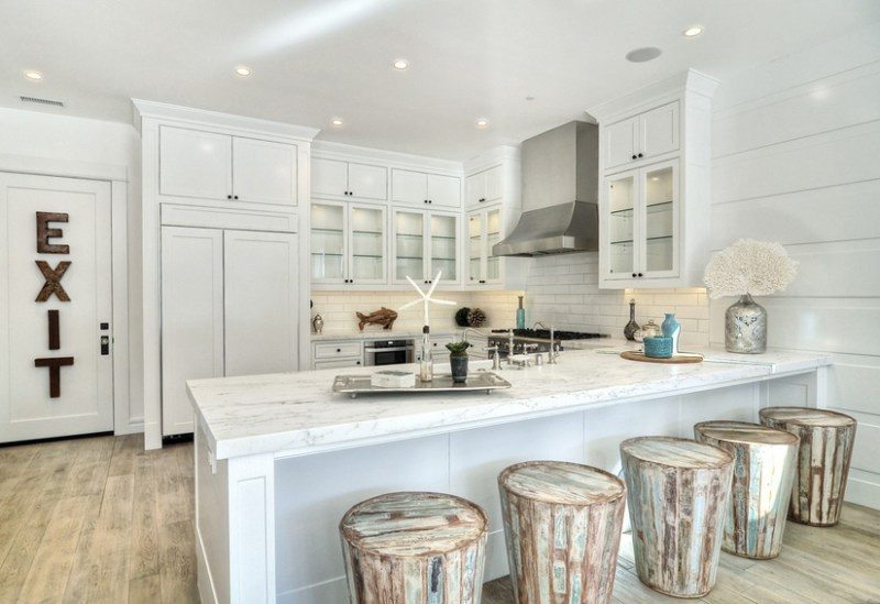 White kitchen with coastal accents. Kitchen with white cabinet and bar stools