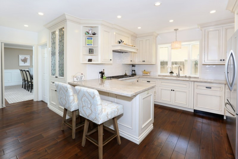 Small white kitchen with dark hardwood flooring and white bar stools