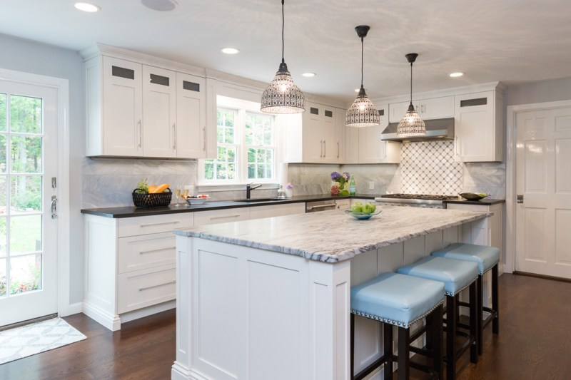 White kitchen light blue bar stools and hardwood floors. Kitchen with dome pendant lights over white kitchen island with marble countertop