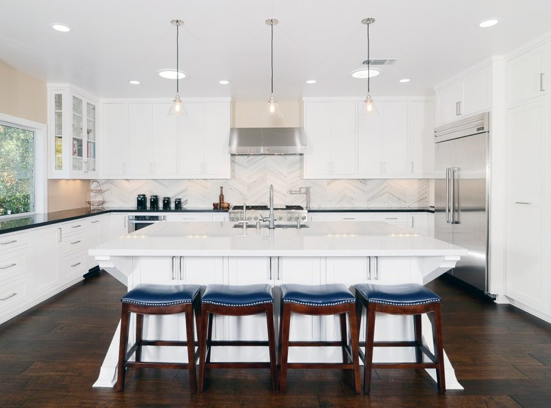 White kitchen with blue leather bar stools and hardwood floors. Kitchen with mini pendant lights over large kitchen island with white countertop