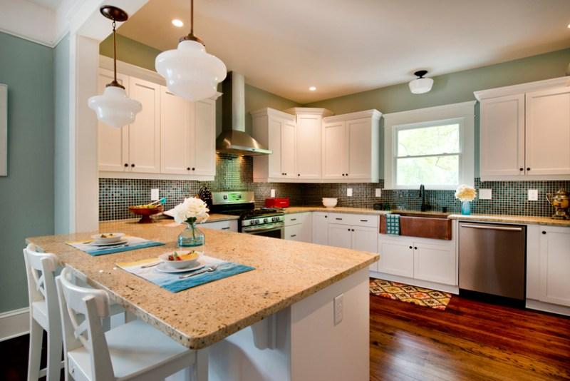 Small white kitchen with white bar stools and green mosaic tile backsplash