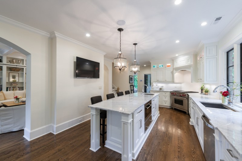 White kitchen with laminate wood flooring. Kitchen with drum shade chandeliers over long narrow kitchen island with marble countertops